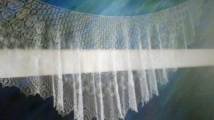 A white lace shawl, so delicate it is translucent, hangs in front of a mural painted like the sea.