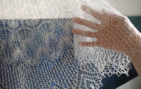 A close up of the bottom hem of a fine lace shawl; the hand holding it up is clearly visible through the fabric.