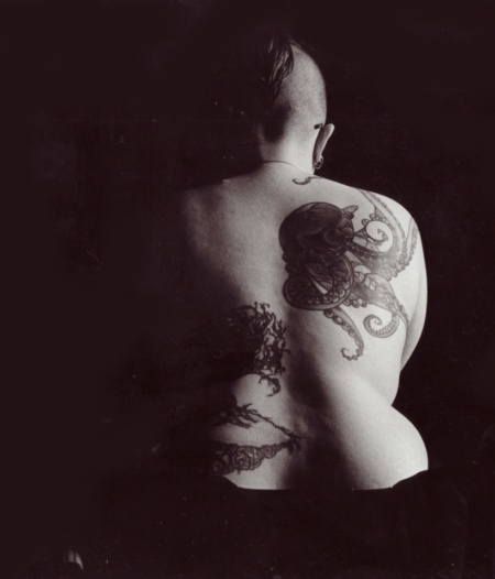 Chiaroscuro black and white image of Toby's bare back, with large octopus and tree tattoos, wheelchair wheels barely visible