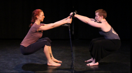 Two dancers squat low in counterbalance, each holding on to forearm crutches that stand upright between them.