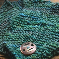 Close up of a sea-green chunky knit cowl with a silver button