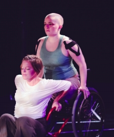 Toby in a manual wheelchair and a dancer crouched on the floor both push up off the frame of the chair