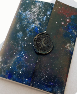 a small booklet painted in blue-black galaxy textures, wraparound cover sealed with black wax