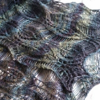 A leafy lace stole in tones of muted blues, greens, and purples