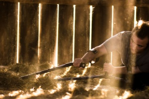 Floor level shot of Toby kneeling to right, crutches out to viewer's left, in the straw floor of a barn. Rich gold sunlight comes in shafts between the barn board slats.