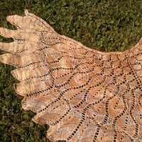 A brown lace shawl in the shape of wings, lying on grass