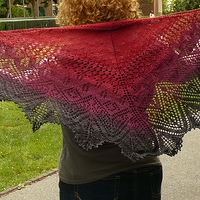 A curly-haired woman is pulling a red and purple lace shawl around her shoulders
