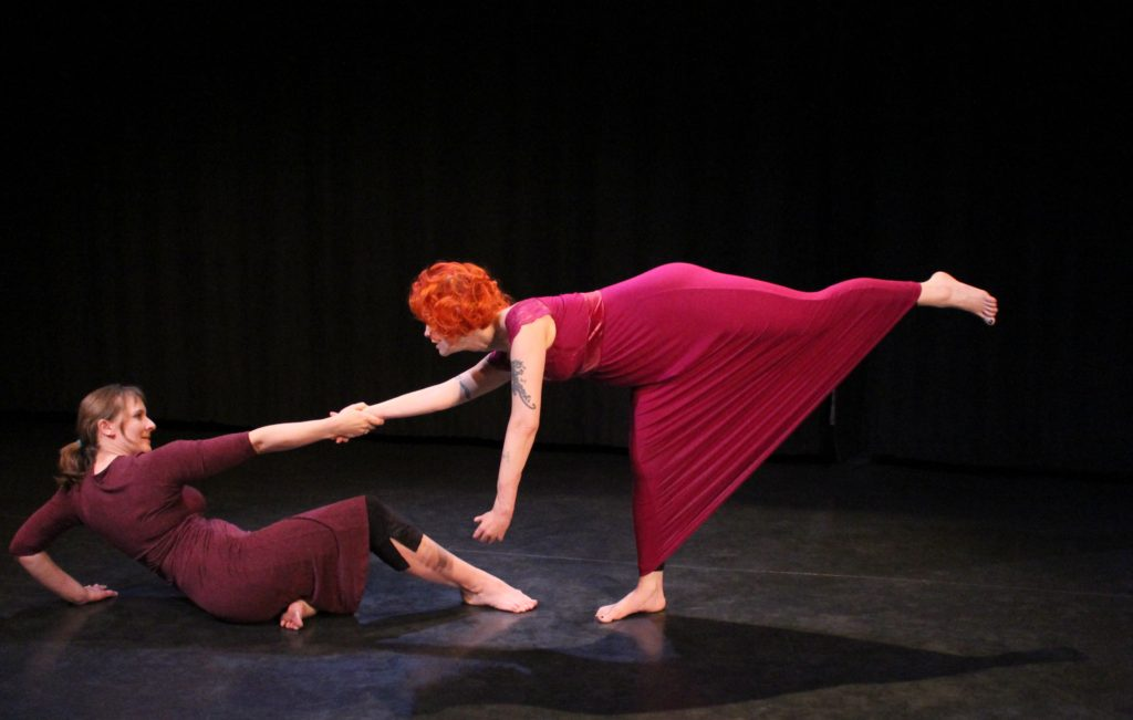 Two women in maroon dresses; one reclines on the floor, the other faces her in a an arabesque. They hold right hands to balance.
