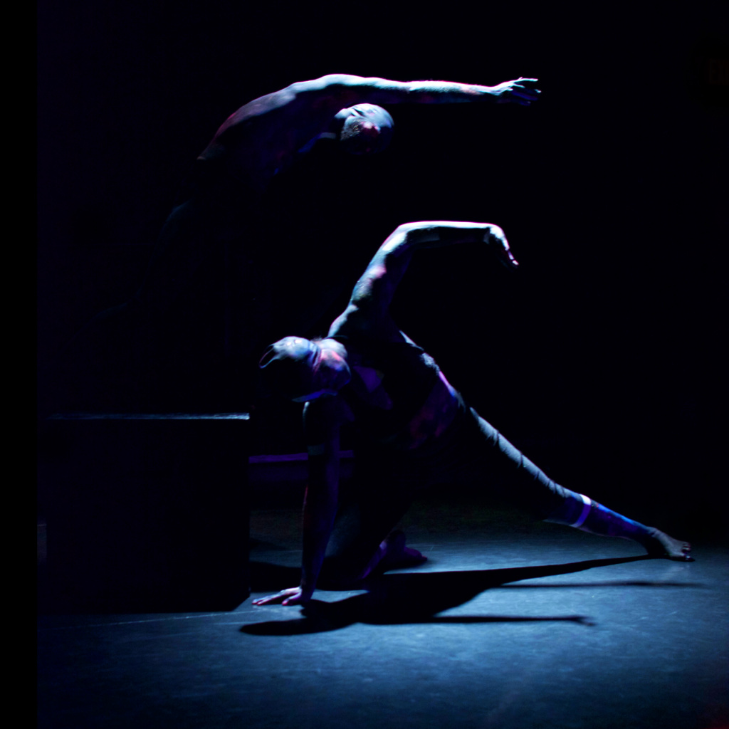 two dancers barely visible as highlighted angular limbs in a pool of light