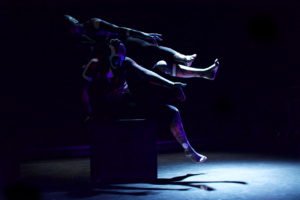 two dancers seated on dark shapes under stark spotlight, arms and legs raised at awkward angles