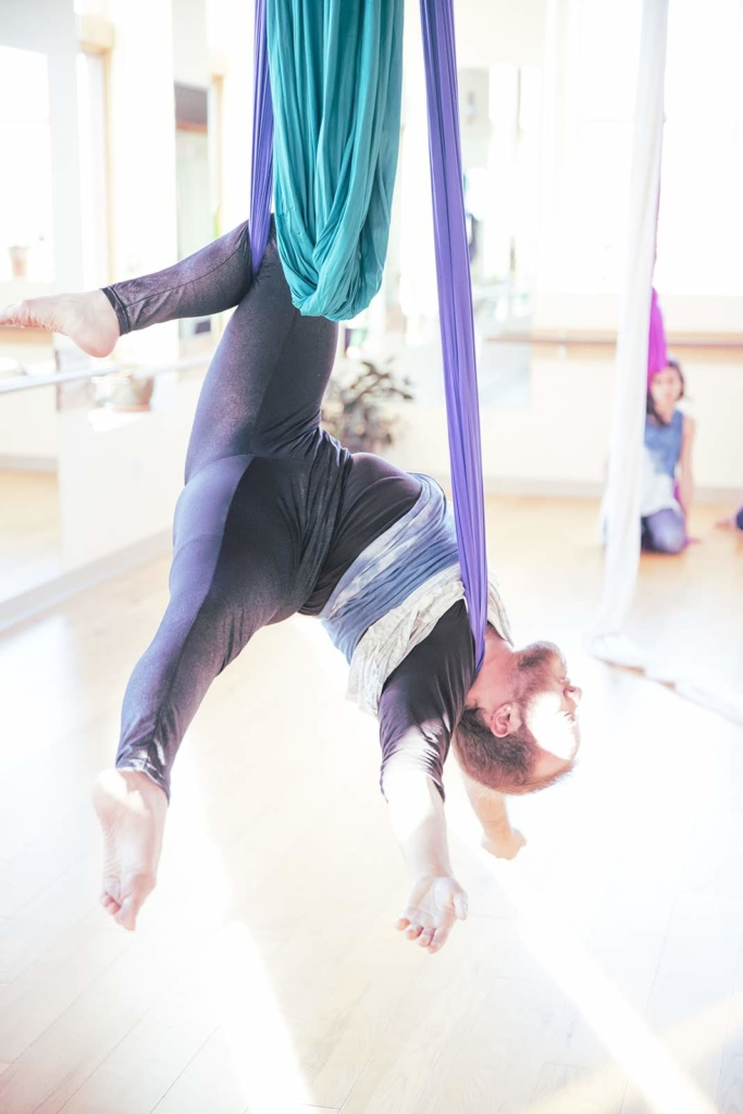 Toby hanging upside down from one knee and one shoulder, limbs relaxed, on purple and green fabrics in a bright studio