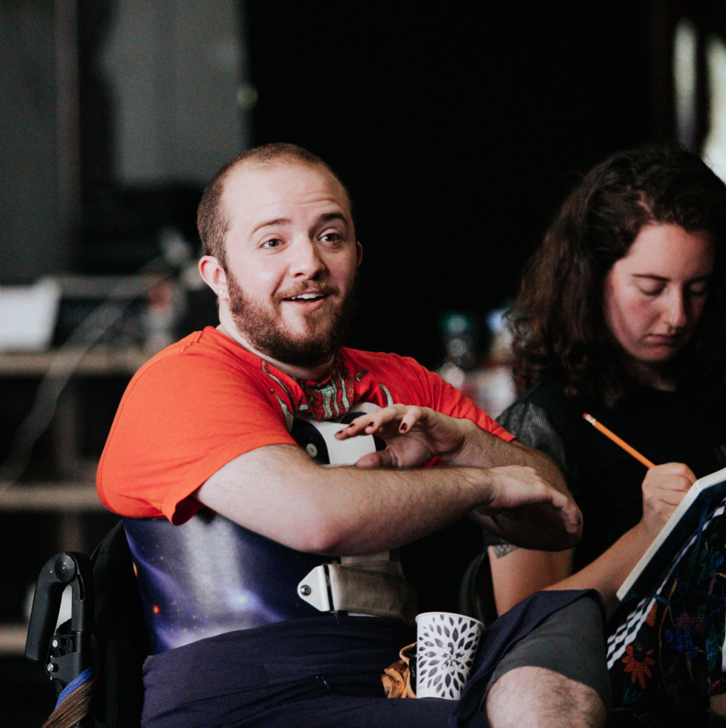 Toby, a white person with a dark beard, sits in their wheelchair among other people. They are in a bright orange tshirt and a purple back brace. They are mid-discussion, mouth open, eyebrows raised, both hands gesturing across their body.