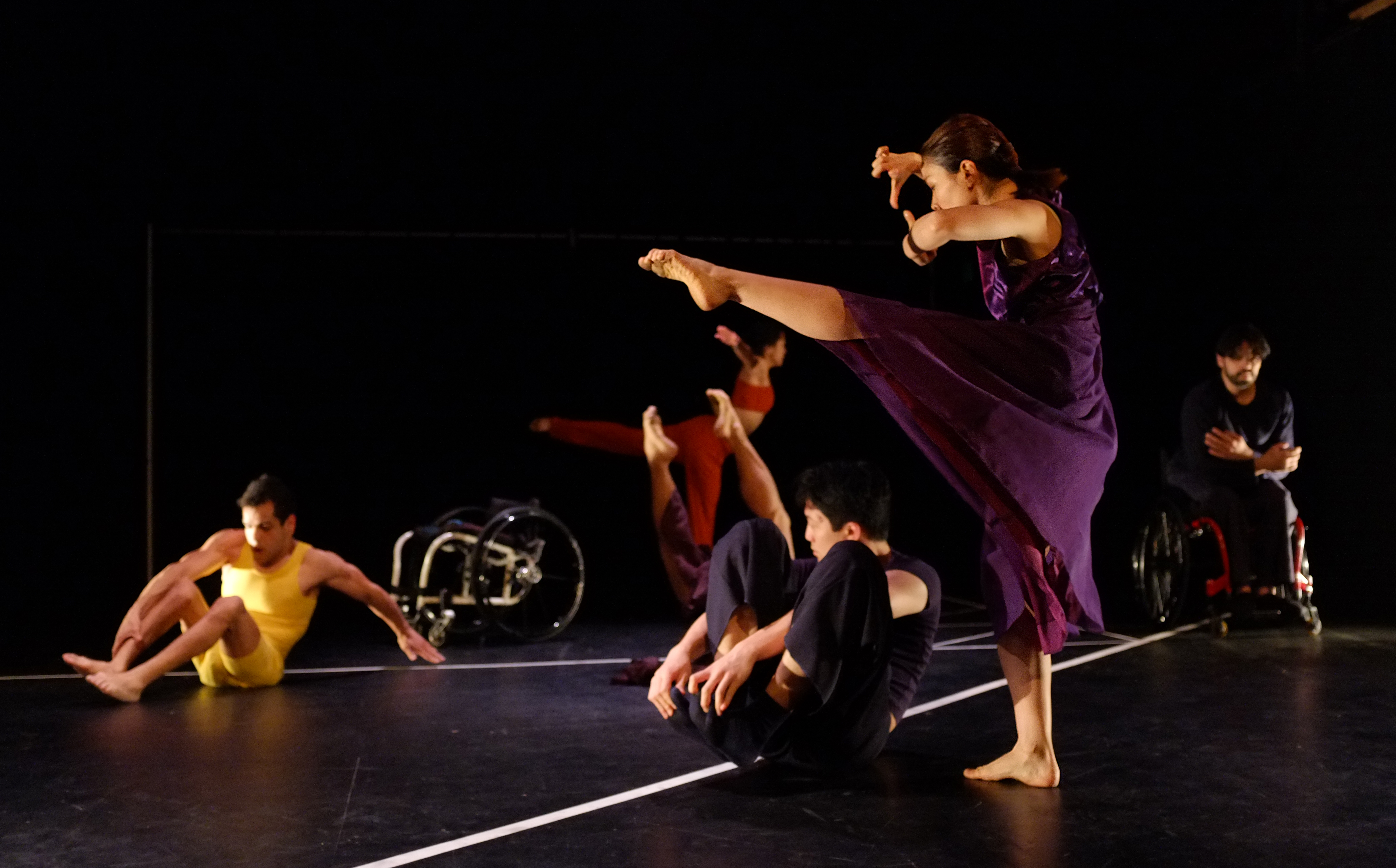 Five dancers are visible in a starkly side-lit dark stage. Each wears a solid color: gold, red, blue, or purple. They range from floor, sitting, to standing heights, all in motion in dynamic shapes. One dancer is in his wheelchair; another chair sits empty at the back. The floor is divided into angular pieces with strips of thick white tape.