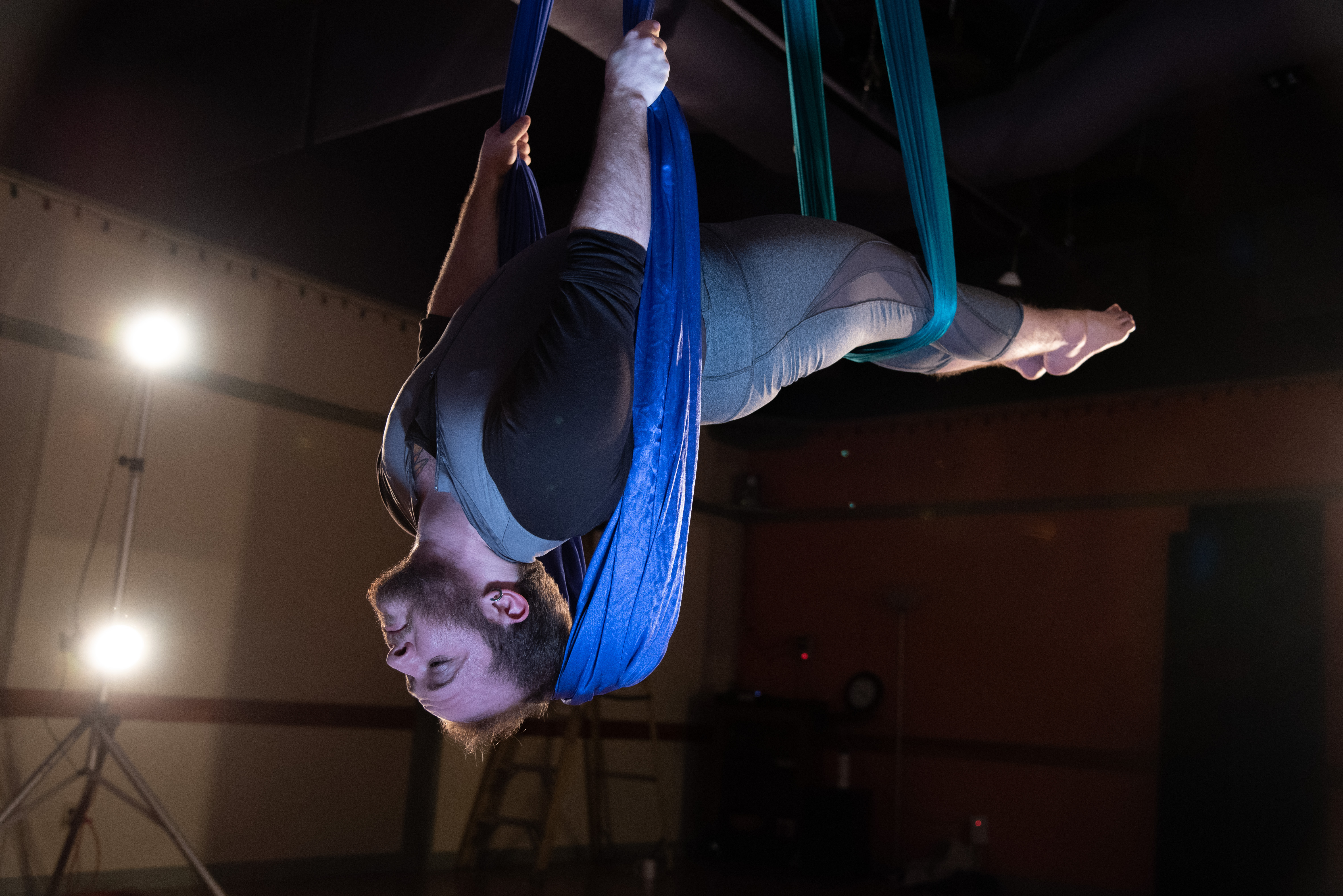 Toby, with dark beard and in grey leggings and long-sleeved leotard, hangs upside down on two aerial fabrics in a shadowy studio. Their legs and lower back are horizontal, and their upper back arches to show their face, eyes closed, relaxed.