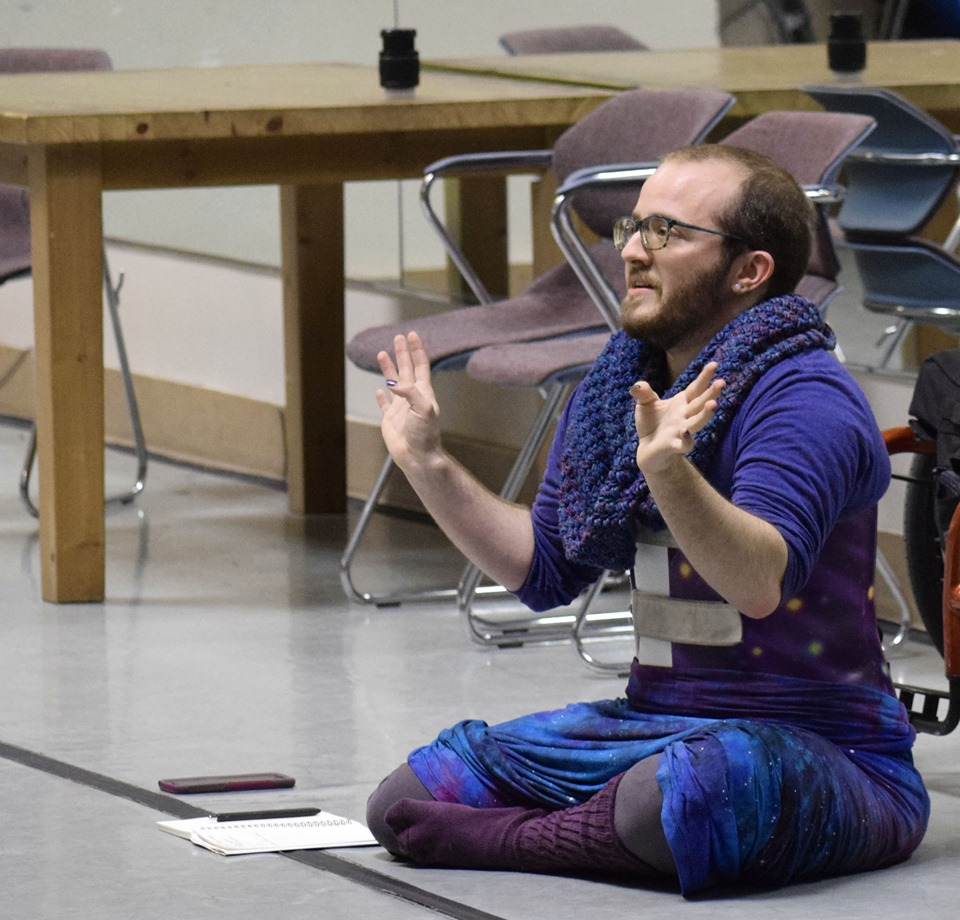 Toby, a white person with a brown beard, sits on a studio floor, legs crossed, hands out in gesture. They are wearing all blue-purples, including a crochet cowl, a back brace, and a long galaxy skirt.