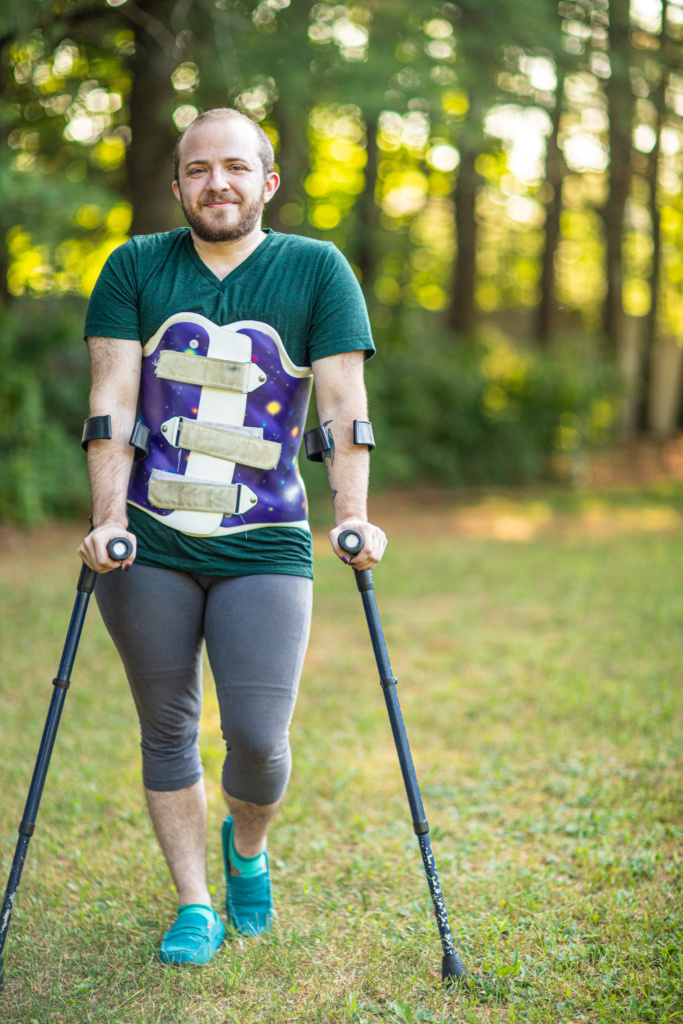 Toby standing on forearm cuff crutches outdoors