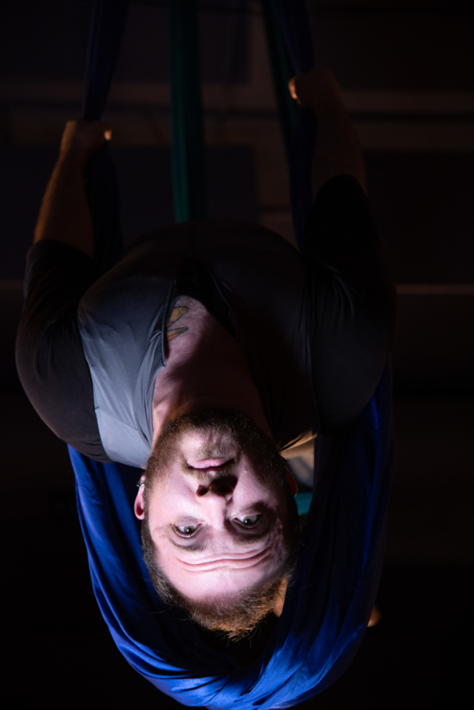 Toby upside down in fabric, face spotlight, brow furrowed
