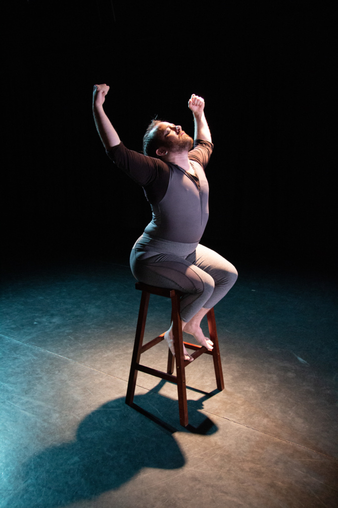 Toby seated on a stool in a spotlight, back arched, arms bent pulling down from overhead, head back and eyes closed