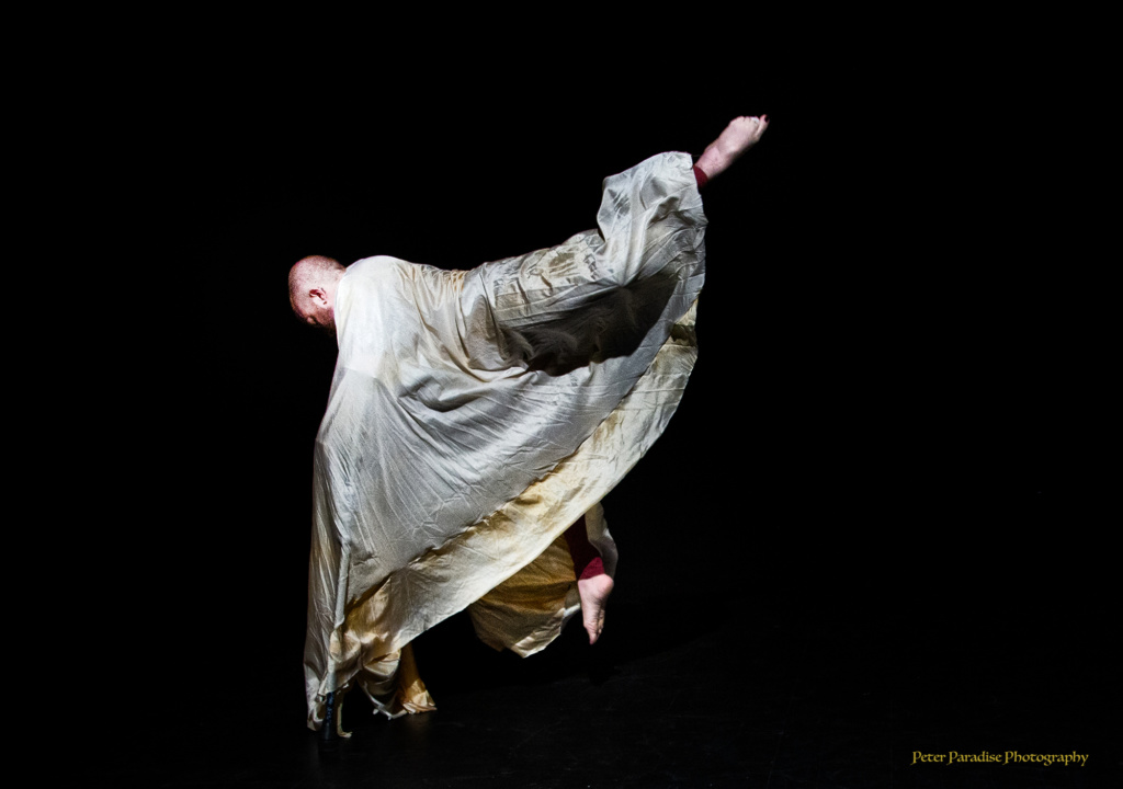 Toby in a shimmery, voluminous, pale yellow cape, leaping on crutches with one leg up behind them, swirling the cape