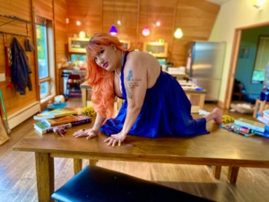 Photo of Neve, a brown-skinned femme person with long orange hair wearing a bright blue dress, on hands and knees on a wooden table