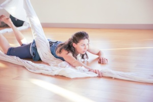 Performance photo of Nicole,  a slender white woman with long brown hair, sliding across a floor on her belly while tangled in white aerial fabric
