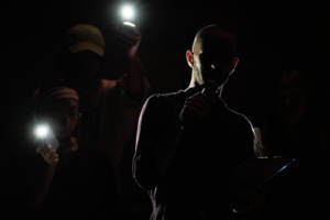 Performance photo of Noah, visible by the backlight around the edges of their body, otherwise in shadow