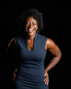 Headshot of Christal, a black woman with short curly hair, hands on her hips and laughing