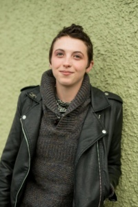 Headshot of Dawn, a white person with very short dark hair, wearing a thick gray sweater and black leather jacket