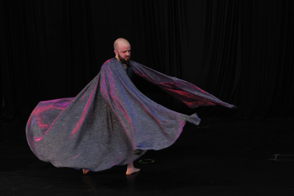 Toby in a swirling voluminous pink-blue-silver shimmery cape, swirling around them mid-turn. Only their head (bald, bearded, pale skin) and their feet are visible. The black floor and wall blend together to look like Toby is floating.